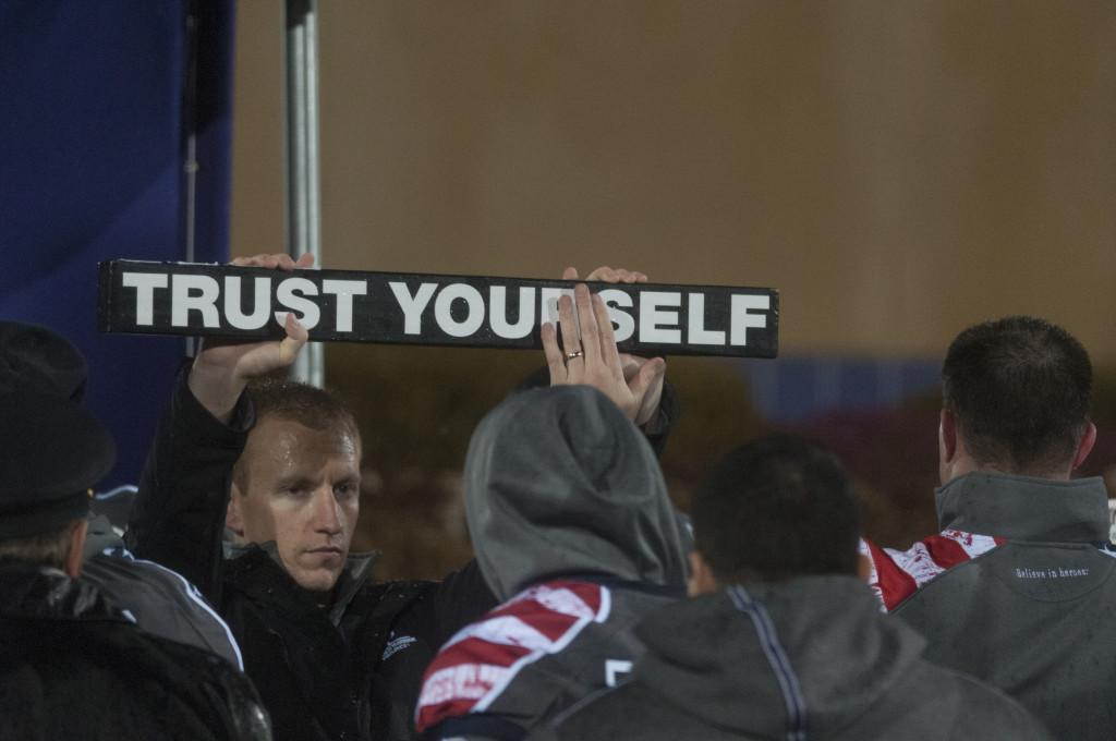 Coach Pat Fitzgerald taps the sign