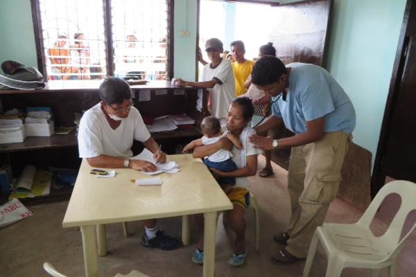 Feinberg School of Medicine Prof. Rahul Khare (far right) tends to a Filipino patient. Khare traveled to the Philippines in the days following Typhoon Haiyan to help provide medical care.