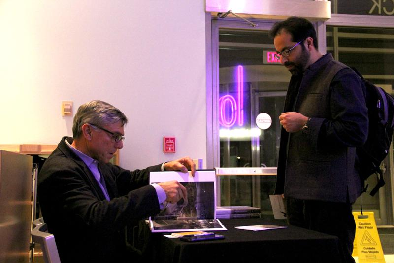 Robert Nickelsberg, photojournalist for TIME Magazine, signs copies of his new book after giving a presentation at Northwestern on photography and Afghanistan. Nickelsberg's book, Afghanistan: A Distant War, features his photography of the region.