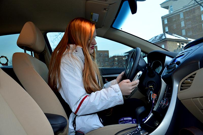 Medill sophomore Shelbie Bostedt checks her phone after parking her car. An Illinois law banning the use of handheld devices while driving went into effect Jan. 1.