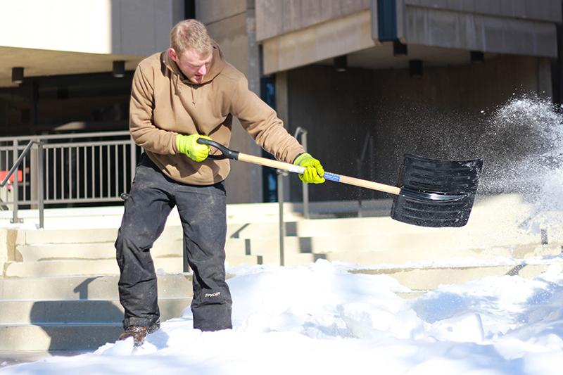 A shoveler removes snow from the steps of University Library. Record area snowfalls left University and Evanston crews working to clear streets and pathways weeks after the polar vortex.