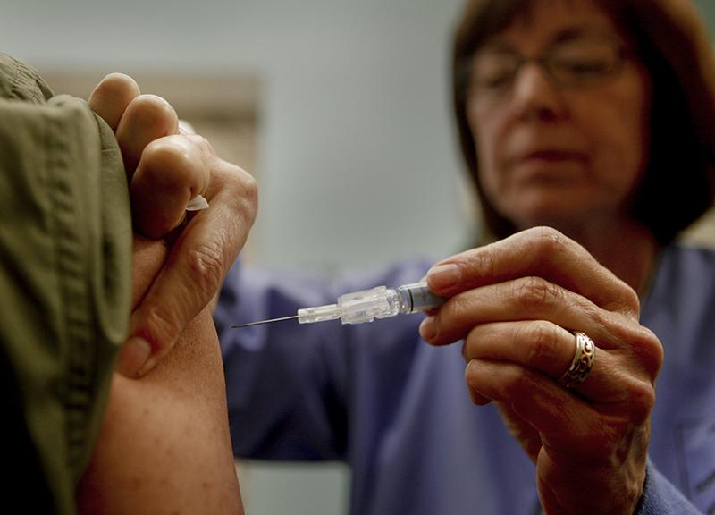 A man gets a vaccination to prevent contracting influenza. There have been 44 ICU admissions and 6 influenza related deaths in Cook County.
