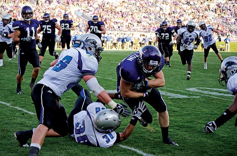 Former+Northwestern+wide+receiver+Drew+Moulton+takes+on+a+defender+in+a+2011+game.+Moulton+expressed+his+support+Tuesday+for+Northwestern+players+in+their+efforts+to+achieve+union+certification.