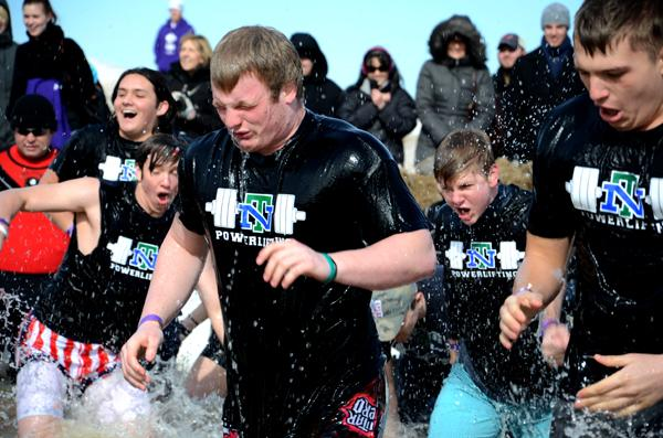 The New Trier Powerlifting Club team runs out of the water Saturday at the Polar Plunge in Evanston.  The event's North Beach participants raised a total of more than $260,000.