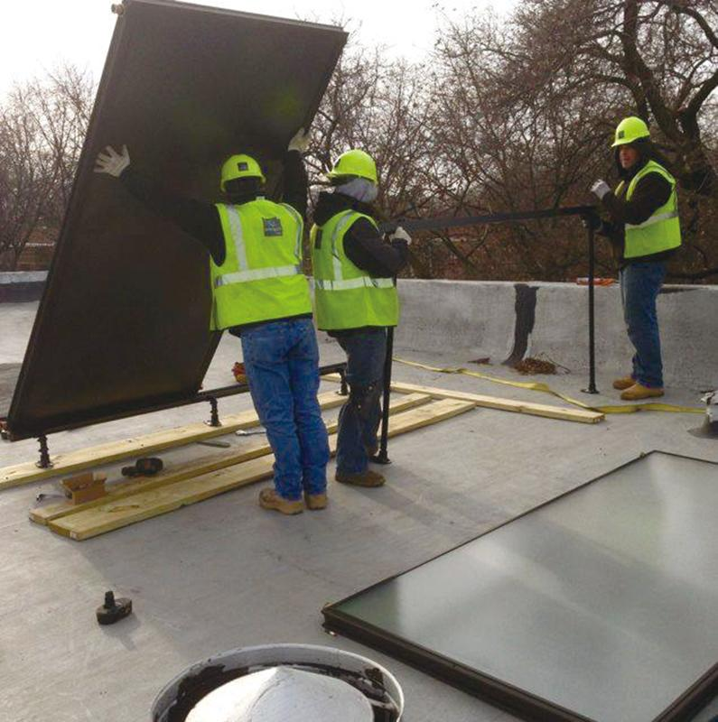 Workers install solar panels on the roof of a building. SHOP allows participants to purchase solar-powered hot water heaters as a group in order to reduce costs.