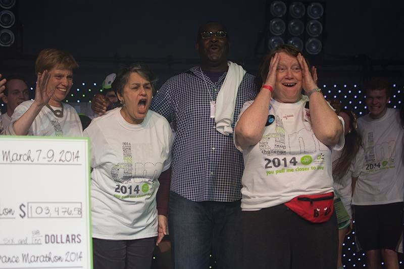 Evanston Community Foundation President Sara Schastok (right) reacts to receiving a check from Dance Marathon for $103,476.58. This was the first time in the two organizations' 17-year partnership ECF had received more than $100,000.