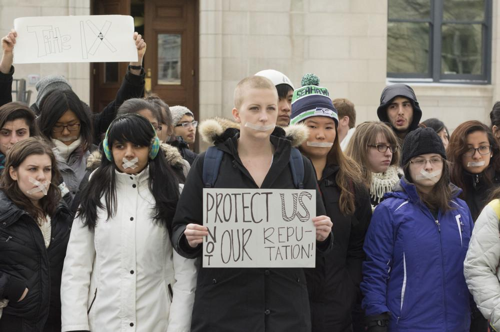 Students taped their mouths and held signs Tuesday afternoon as part of a protest of Northwestern's sexual assault policies. The protesters met at Harris Hall before marching to the office of Weinberg College of Arts and Sciences Dean Sarah Mangelsdorf.
