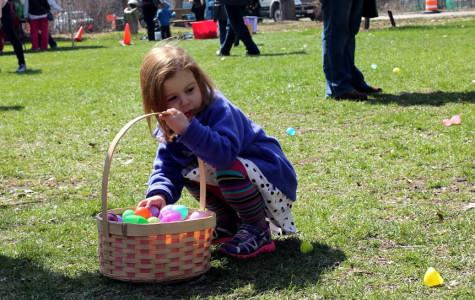 """Children and families help """"Betsy the Bearded Dragon"""" find her misplaced Easter eggs during the annual egg hunt at the Evanston Ecology Center on Saturday. Event volunteer Madeline Maxwell said the egg hunt is an event that community members """"keep coming back to."""" More than 100 participants showed up to search for Easter eggs in the first of four activity blocks."""