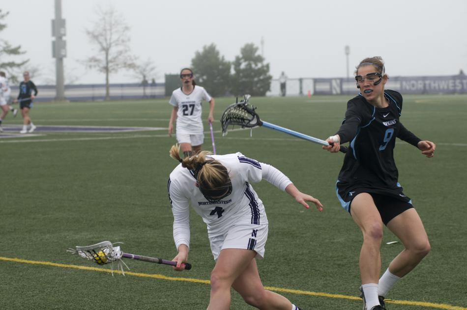 Senior+Kat+DeRonda+gets+knocked+on+the+head+by+a+Johns+Hopkins+player+Sunday.+DeRonda+continued+her+recent+tearing%2C+netting+four+goals%2C+but+Northwestern+lost+12-11+in+double-overtime.%0A