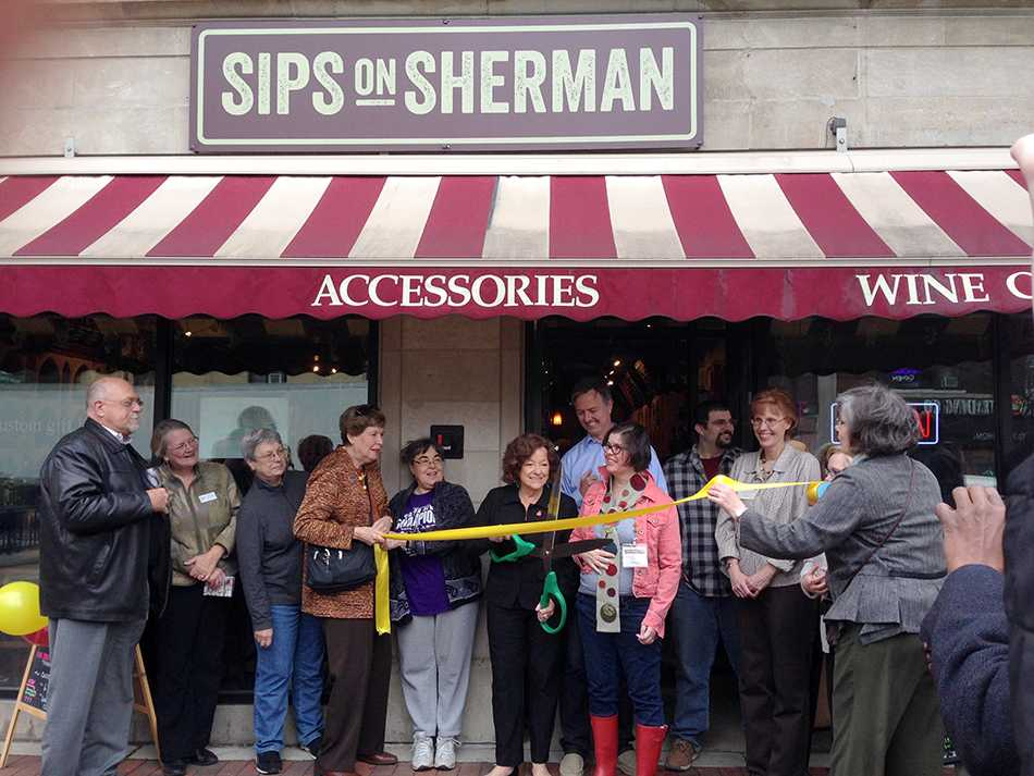 Ald. Ann Rainey (8th) cuts the ribbon at Sips on Sherman's ribbon-cutting celebration as staff and friends look on. The wine shop held its grand re-opening Thursday evening.