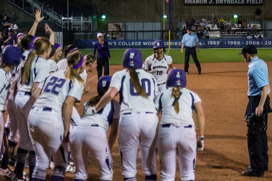 Senior catcher Paige Tonz comes home to an excited mob of teammates after smacking a grand slam in Thursdays win over Michigan State. Northwestern used 6 fifth-inning runs to win 10-4 in the first-ever night game at Sharon J. Drysdale Field.