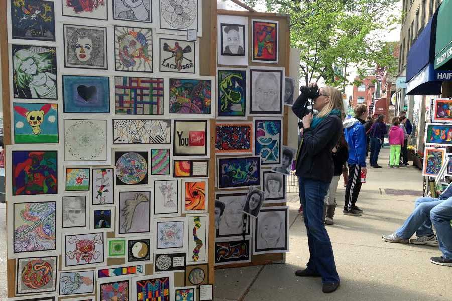 A woman photographs art created by local students at an Evanston festival Saturday hosted by the Young Evanston Artists foundation. Known as YEA! Day, the annual event showcases the work of about 1,000 students from pre-kindergarten through high school.