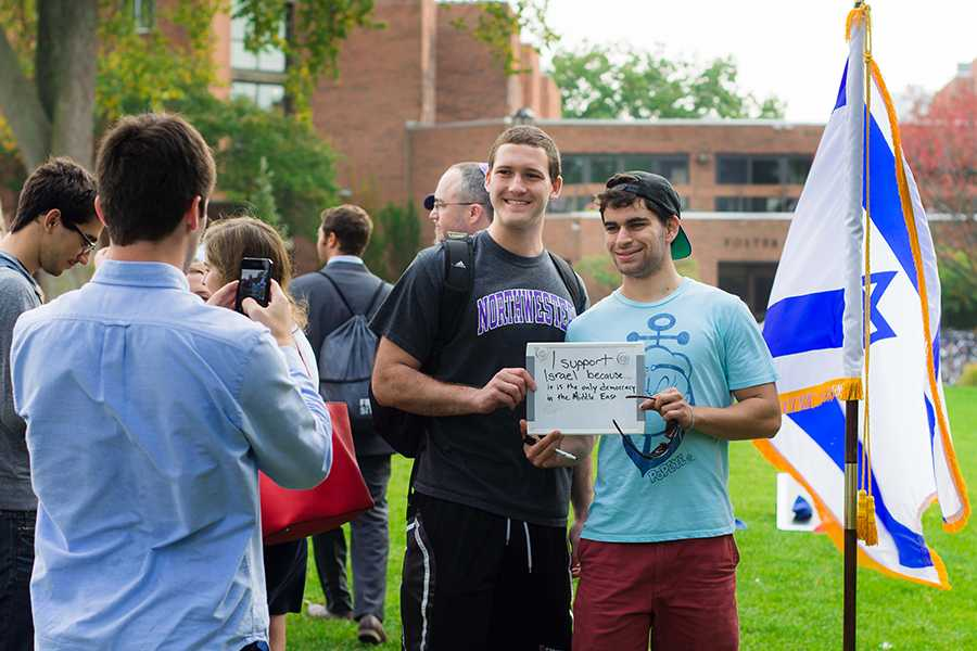 Attendees+pose+for+pictures+with+a+sign+explaining+their+support+for+Israel+at+a+solidarity+picnic.+The+event+was+hosted+by+Fiedler+Hillel+and+the+Israel+on+Campus+Coalition+to+unite+the+Jewish+community+on+campus%2C+organizers+said.