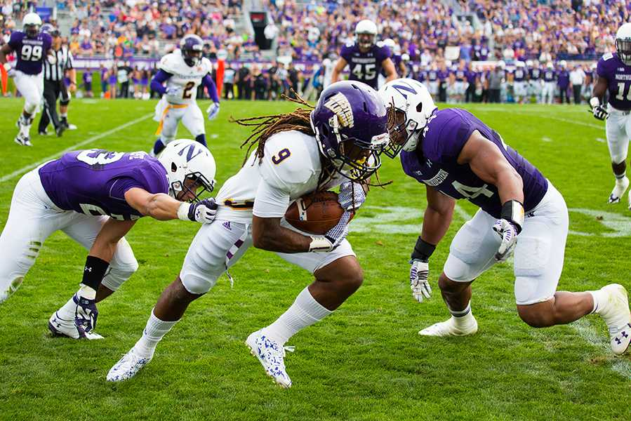 Northwestern's Nick VanHoose and Chi Chi Ariguzo attempt to bring down a Western Illinois ball-carrier. The Wildcats won 24-7 despite giving up more total yards than they gained.