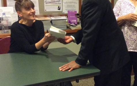"""Mary Barr signs her book for an attendee of her talk Saturday at the Evanston Public Library, 1703 Orrington Ave. In front of about 100 people, Barr read an excerpt from her book, """"Friends Disappear: The Battle for Racial Equality in Evanston,"""" which details the history of the city's racial issues."""