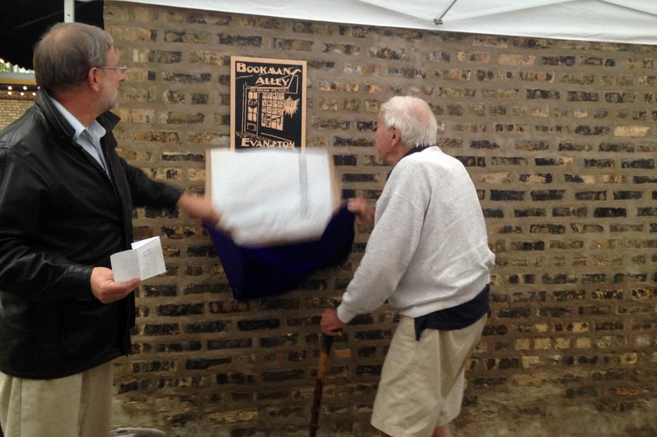 Roger Carlson, right, is presented a plaque outside of Bookends & Beginnings, located in an alley off of Sherman Avenue. The building once housed Carlson's bookstore Bookman's Alley, which closed last year after more than 30 years in Evanston.
