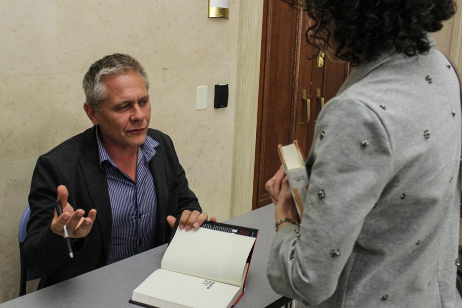 """Author Walter Kirn signs a copy of his book after speaking Saturday as part of the Chicago Humanities Festival. His memoir, """"Blood Will Out,"""" details his interactions with Christian Gerhartsreiter, who conned many under the name Clark Rockefeller."""