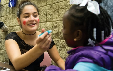 Communication freshman Allison Towbes paints the face of a trick-or-treater at Project Pumpkin on Thursday night. The event, sponsored by Northwestern Community Development Corps, provided trick-or-treating and games for Chicago-area children.