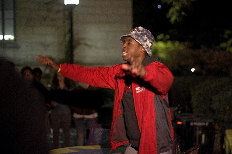 Student performer Prez Harris (McCormick sophomore Randall Harris) raps Wednesday night at The Rock as part of a demonstration to express anger over the shooting of an unarmed black teenager in Ferguson, Missouri in August. About 50 students attended the event, wearing red armbands and listening to student musical and spoken-word acts.