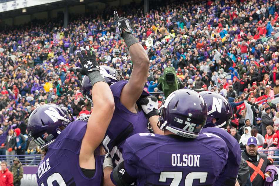 Junior running back Miles Shuler celebrates with teammates after his 16-yard run on a third-quarter reverse play. The play was one of several aggressive calls from coach Pat Fitzgerald and offensive coordinator Mick McCall.