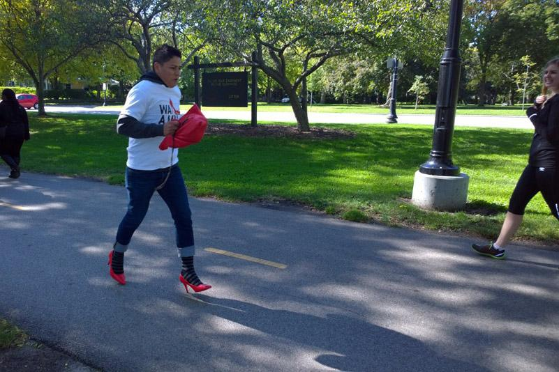 """A man walks in heels Sunday through Evanston's Centennial Park for """"Walk a Mile in Her Shoes."""" The event, hosted by nonprofit Northwest Center Against Sexual Assault, aimed to raise awareness of sexual assault and bring support to survivors."""