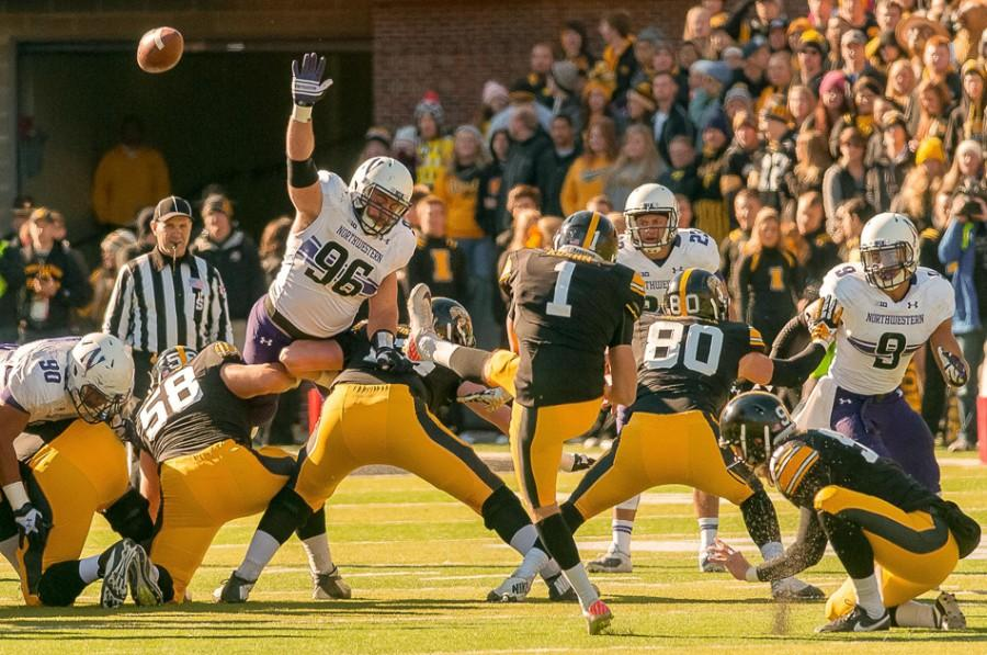 Junior defensive lineman Max Chapman jumps at a pass during Northwestern's game against Iowa last Saturday. The junior intimidates offensive linemen with a beard he's been growing since July 4.