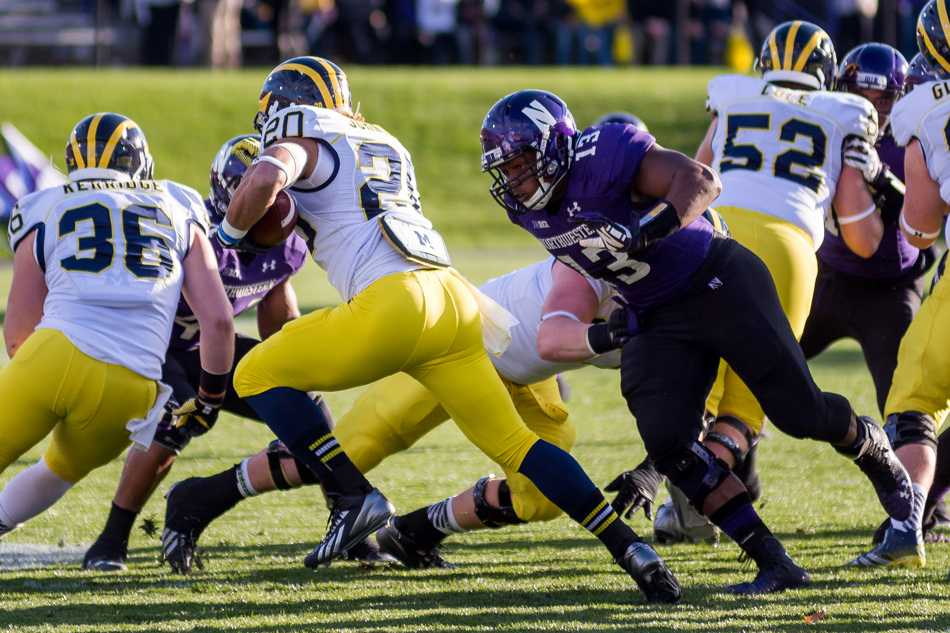 Junior defensive end Deonte Gibson lunges at a Michigan ball-handler. When not battling injuries, Gibson has provided steady play on the defensive line during his three years on the field for Northwestern.