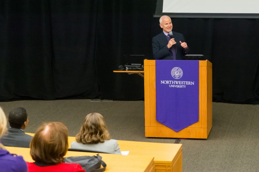 "University President Morton Schapiro speaks at the ""Kits and Cats: Collaboration in the 21st Century"" discussion Thursday evening. The talk, attended by many Evanston and Northwestern officials, highlighted growing cooperation between ETHS and the University."