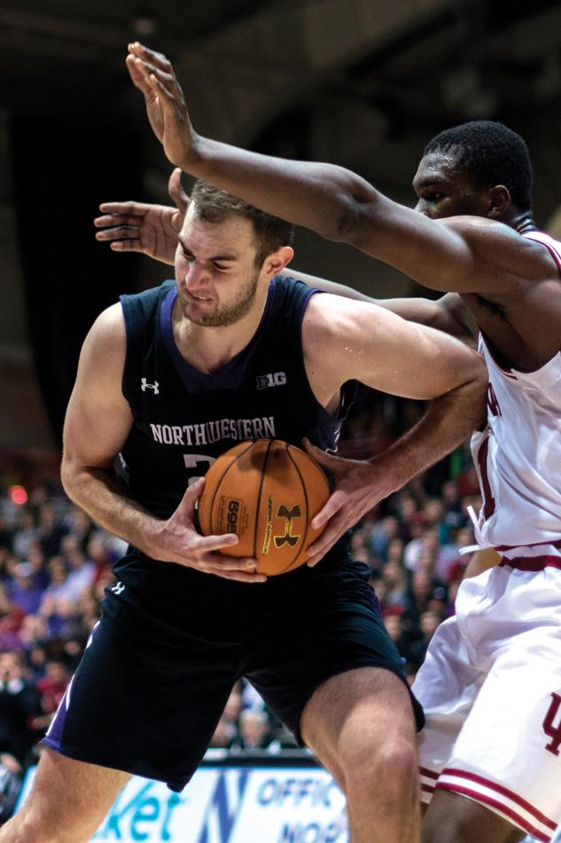 Alex Olah muscles his way around a defender. The junior center is expected to play a larger role in his second year in coach Chris Collins' system.