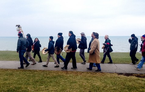 A group of Evanston and Chicago community members march along The Lakefill on Saturday afternoon. The crowd gathered for a commemoration of the Sand Creek Massacre held by the Native American and Indigenous Students Alliance.