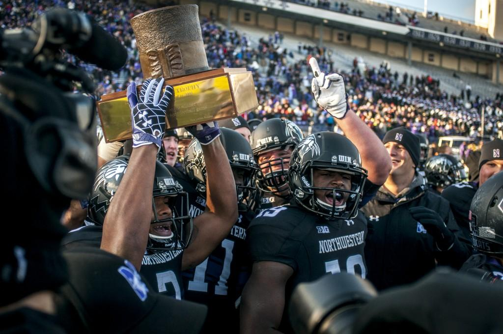Northwestern players hoist the Land of Lincoln Trophy following the team's 50-14 defeat of Illinois in 2012. The Wildcats have defeated the Fighting Illini the past two seasons.