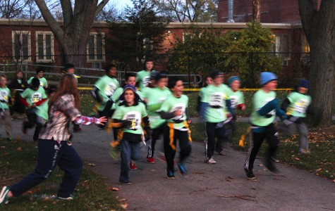 Children and families run from volunteers dressed as zombies during Evanston's first Zombie Scramble. The event was hosted by the city's Parks, Recreation and Community Services department and included races for both families and adults.