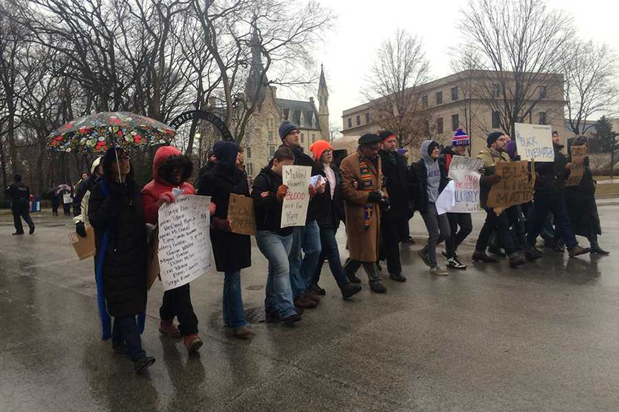 Members of the Garrett-Evangelical Theological Seminary march in the rain down Chicago Avenue on Monday morning. The demonstration, held to protest the grand jury decisions in Missouri and New York, caused police officers to divert car traffic to ensure participants' safety.