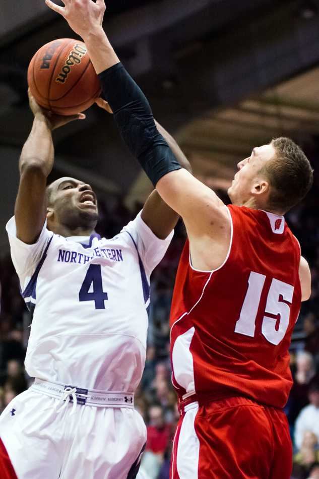 Vic Law attempts a shot against Wisconsin forward Sam Dekker. The freshman has struggled to adjust offensively to the college game, but his athletic ability is still shining through for the Cats.