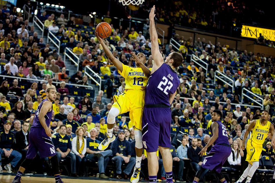 Michigan guard Muhammad-Ali Abdur-Rahkman drives against center Alex Olah. The Northwestern junior was a dominant force on both ends against the Wolverines, especially with 22 points on 9-12 FG on offense, but it wasn't enough to stop another debilitating Wildcats defeat.