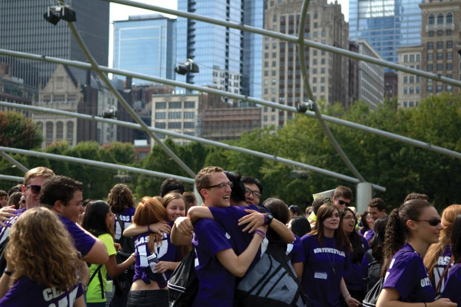 Three freshmen embrace each other at Millenium Park during Wildcat Welcome's Purple Pride event. After increases in recent years, the total number of applications Northwestern received dropped by almost 5 percent this year.