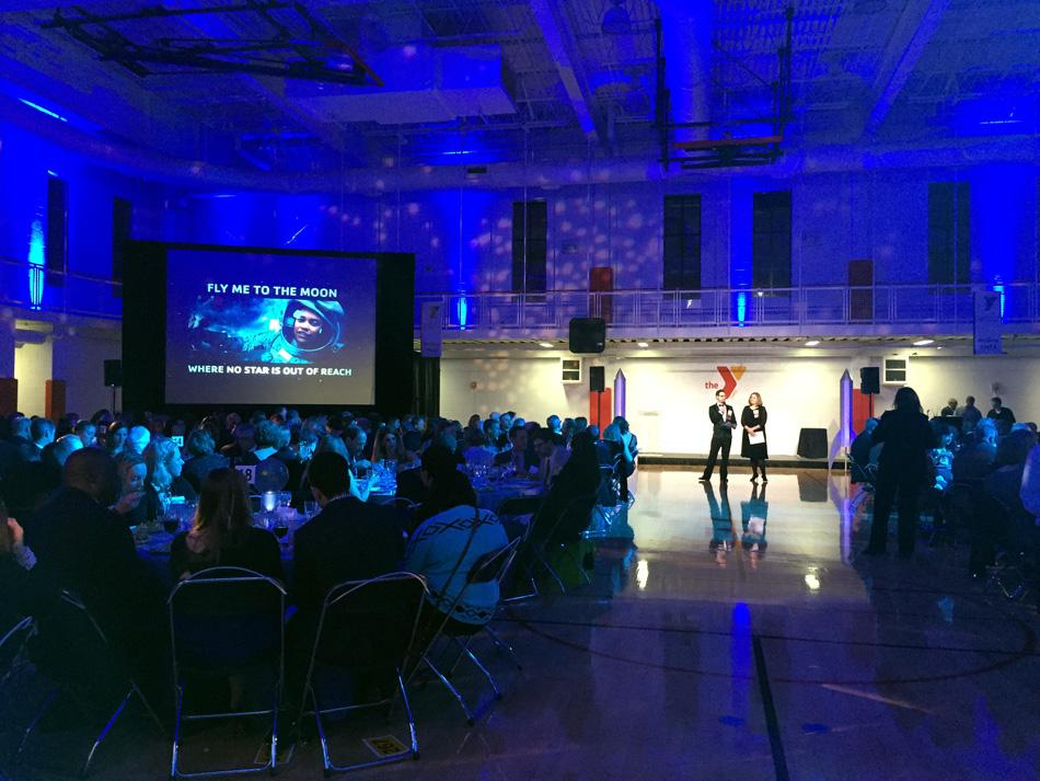 Attendees and organizers participate in a live auction at the McGaw YMCA on Saturday. The McGaw YMCA held a gala that recognized a foundation and NU professor for their contribution to Evanston youth.