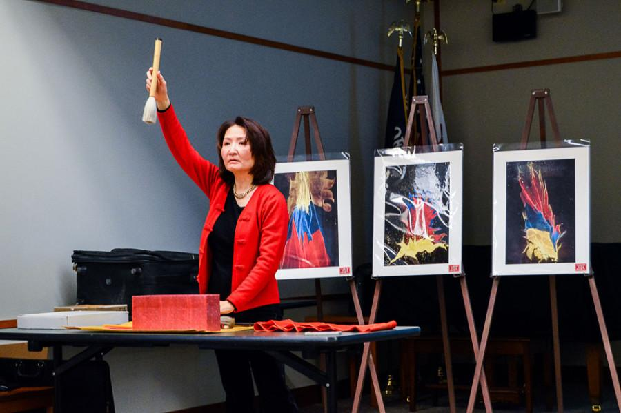 Amy Lee Segami demonstrates the techniques used for suminagashi, an ancient Japanese art form. Segami spoke on the art form at the Evanston Public Library Sunday.
