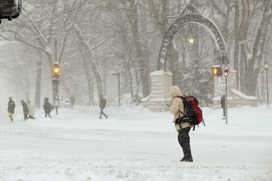 Students trudge past The Arch as snow blows by Sunday afternoon. The National Weather Service predicted 10 to 16 inches of snow for Sunday evening.