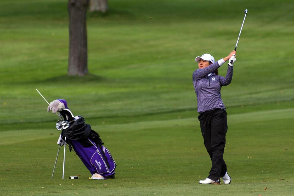 Suchaya Tangkamolprasert poses after an iron shot. The junior posted the lowest scoring average on the team in the fall but is just one of several talented NU golfers.