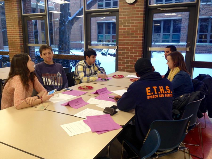 Evanston Township High School senior MD Shelton talks with Northwestern student group members. The groups met up at ETHS's cafeteria as part of an ASG-organized symposium for NU and ETHS students.