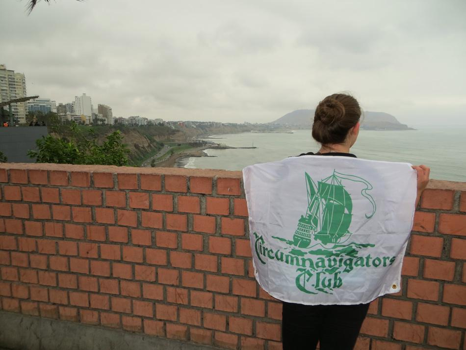 Weinberg junior Elizabeth Larsen poses with the Circumnavigators Club flag while on her global trip this summer. After receiving the Club's $9,000 annual grant, Larsen traveled to seven countries and five continents.