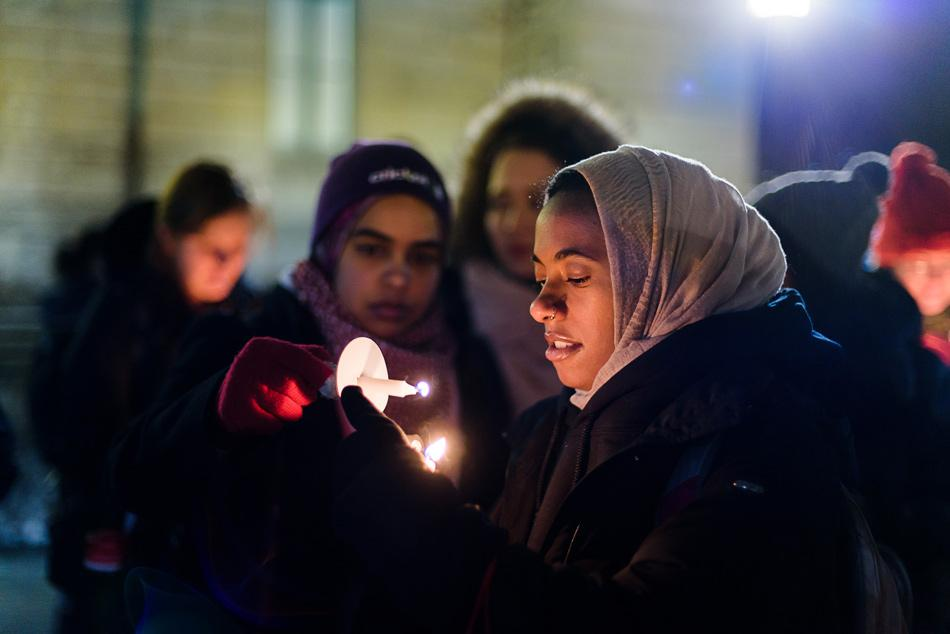 Students light candles before a vigil at The Rock on Wednesday. The vigil, hosted by the Muslim-cultural Students Association, was held in honor of three Muslim students who were fatally shot in Chapel Hill, North Carolina, on Tuesday.