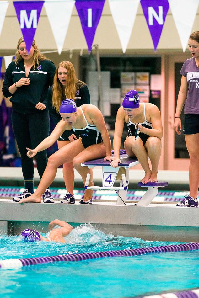 Northwestern swimmers cheer on a teammate during a heat. The Wildcats placed 10th out of 13 teams at the Big Ten Championships on Saturday.
