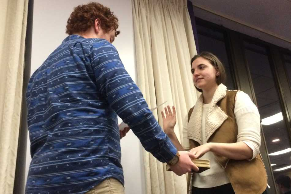 Speaker Noah Star swears in Weinberg junior Mackenzie Schneider as vice president for A-status finances at Senate's March 11 meeting. She will oversee funds given to A-status student groups​.