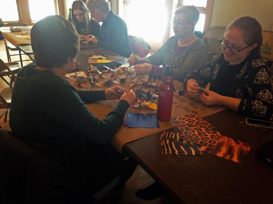 """Evanston resident Jessica Iverson (right) and others fold origami at """"Flight for Peace."""" The event was held at the Evanston Ecology Center and is a part of the Winter HeARTh series."""