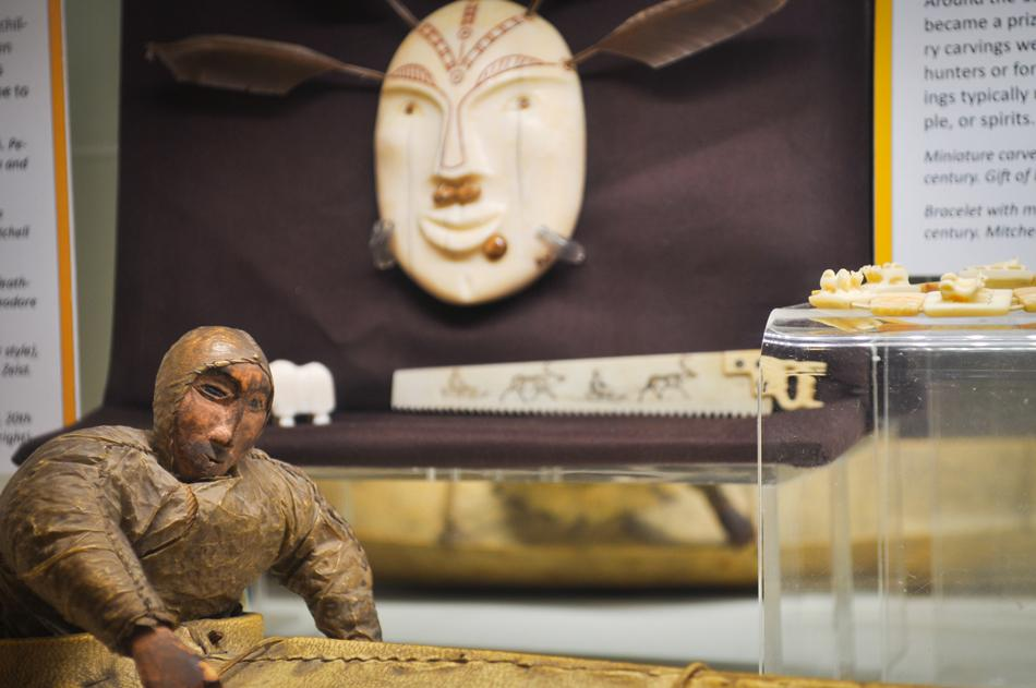 The Mitchell Museum of the American Indian displays a figure of a fisherman wearing a seal-gut parka in a kayak and an ivory mask, both from the arctic or subarctic region. The museum unveiled its exhibit of miniatures Saturday.