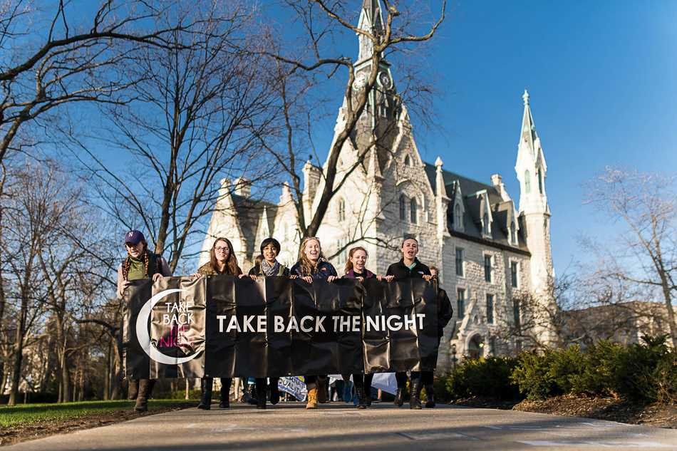 Students march through campus Thursday to raise awareness about sexual violence. Nearly 80 students participated in the Take Back the Night event.