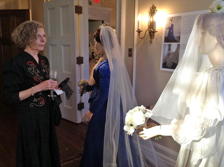 Evanston resident Susan Moss views a 19th-century wedding dress at the Evanston History Center's new exhibit. The center held a wedding reception-themed opening event Thursday night for the exhibit.