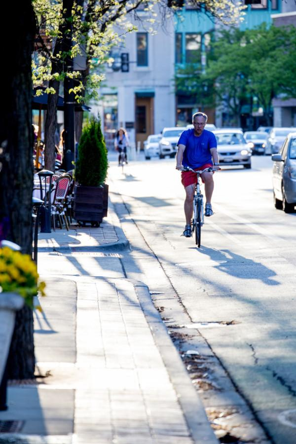 """A man rides his bike in a buffered bike lane. The city has introduced several new programs, such as the """"Let's Roll Together"""" campaign, to encourage safe biking."""